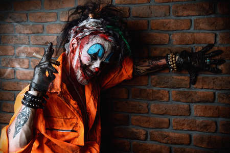 Halloween. Portrait of a bloodthirsty clown man over dark brick wall. Male zombie clown. Horror, thriller film. Stock Photo - 85979170