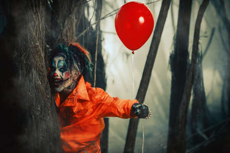 Scary man clown stained in blood in a night forest with a balloon. Male zombie clown. Halloween. Horror. Stock fotó
