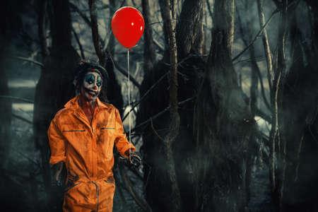 무서운 남자 광대 풍선으로 밤 포리스트의 혈액에서 스테인드. 남성 좀비 광대입니다. 할로윈. 공포. 스톡 콘텐츠