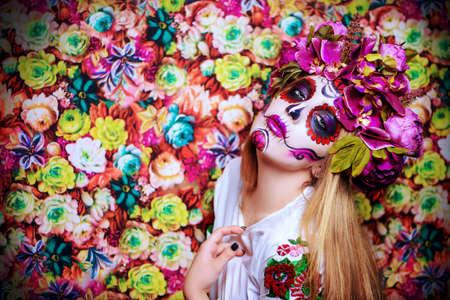 Dia de los muertos. Dag van de Doden. Vrouw met de make-up van de suikerschedel op een bloemenachtergrond. Calavera Catrina. Halloween.