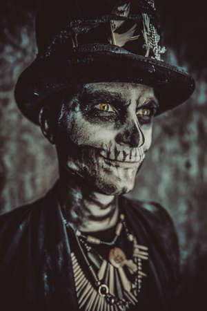 Close-up portrait of a man with a skull makeup dressed in a tail-coat and a top-hat. Baron Saturday. Baron Samedi. Dia de los muertos. Day of The Dead. Halloween. Stock Photo - 86050644