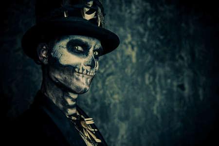 Close-up portret van een man met een schedel make-up gekleed in een tail-coat en een top-hoed. Baron zaterdag. Baron Samedi. Dia de los muertos. Dag van de Doden. Halloween.