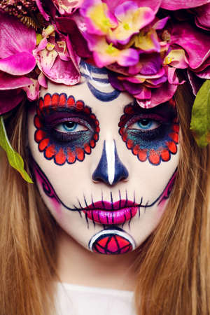 Closeup portrait of Calavera Catrina. Young woman with sugar skull makeup. Dia de los muertos. Day of The Dead. Halloween.