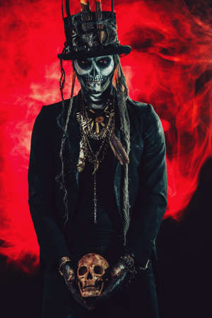 A man with a skull makeup dressed in a tail-coat and a top-hat. Baron Saturday. Baron Samedi. Dia de los muertos. Day of The Dead. Halloween. Stock Photo - 86130675