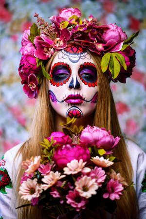 Dia de los muertos. Dag van de Doden. Vrouw met de make-up van de suikerschedel op een bloemenachtergrond. Calavera Catrina. Halloween. Stockfoto - 86180780
