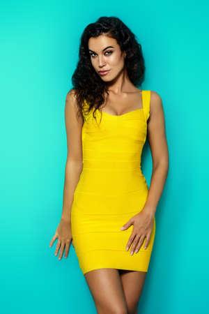 아름다움, 패션 쐈어. 파란색 배경에 노란 드레스에 아름 다운 날씬한 검게 여자. 갈색 머리카락.
