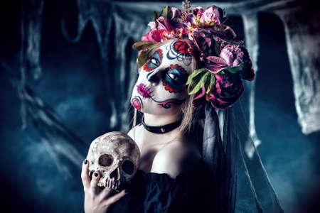Calavera Catrina in zwarte kleding die een schedel over donkere enge achtergrond houden. Suiker schedel make-up. Dia de los muertos. Dag van de Doden. Halloween.