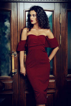 도시 거리에 우아한 부르고뉴 드레스를 입은 매력적인 갈색 머리 여자. 아름다움, 패션 개념입니다. 화장품 및 메이크업.