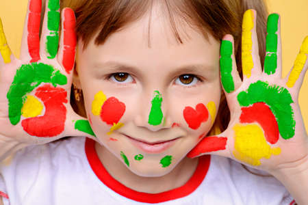 Funny little girl with paints on her face and palms. Drawing. Yellow background.