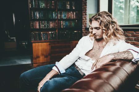 소파에 누워 흰 셔츠에 잘 생긴 섹시 한 젊은 남자. 남자의 아름다움, 패션. 머리카락, 헤어 스타일. 스톡 콘텐츠