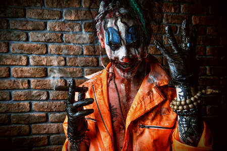 Halloween. Portrait of a bloodthirsty clown man over dark brick wall. Male zombie clown. Horror, thriller film. Reklamní fotografie