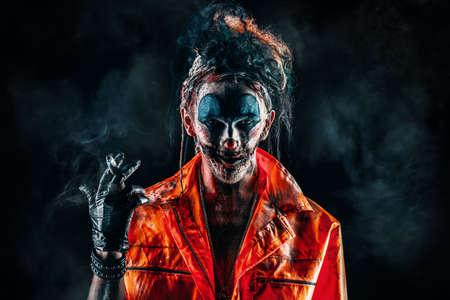 할로윈. 검정 배경 위에 시가 흡연 혐오 광대 남자의 초상화. 남성 좀비 광대입니다. 공포, 스릴러 영화.