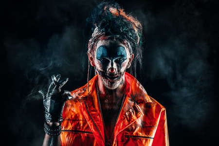 Halloween. Portrait of a disgusting clown man smoking a cigar over black background. Male zombie clown. Horror, thriller film. Stock fotó - 86281998