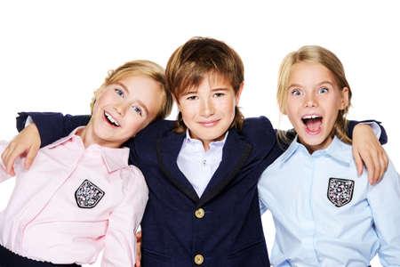 学校のファッション。3 人の陽気な子供学校制服で一緒に楽しんで。白い背景に分離されました。領域をコピーします。