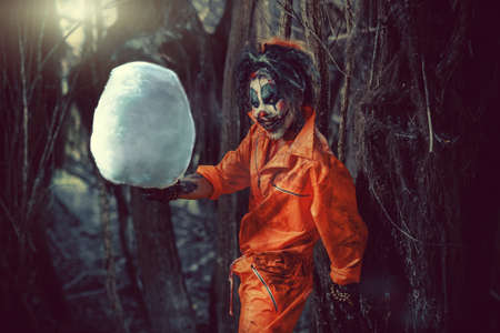 Bloodthirsty clown man in a night forest with a candy-floss. Halloween. Horror. Stock Photo - 86370312