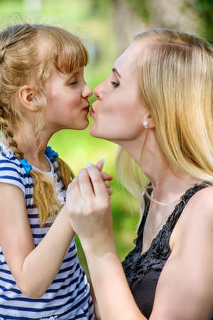 Family concept. Happy mother is kissing her little daughter. Summer holidays. Reklamní fotografie