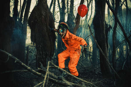 Scary man clown stained in blood in a night forest with a balloon. Male zombie clown. Halloween. Horror. Stock Photo