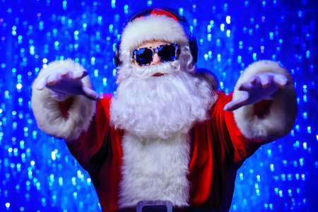 DJ Santa Claus in sunglasses and headphones. Christmas songs and music. Disco lights in the background. Banco de Imagens