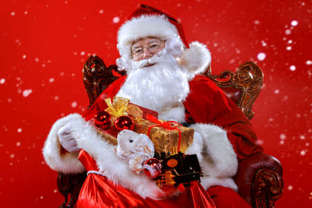 Christmas and New Year concept. Portrait of good old Santa Claus sitting in his armchair. Red background. 版權商用圖片