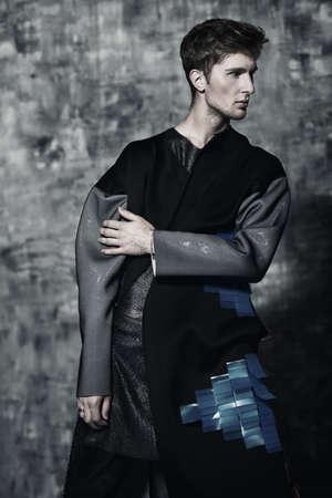 남자의 아름다움, 패션. 세련 된 옷을 입고 포즈 잘 생긴 남자 모델의 초상화. 스튜디오 촬영.