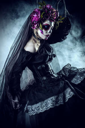 Calavera Catrina in black dress over dark background. Sugar skull makeup. Dia de los muertos. Day of The Dead. Halloween.