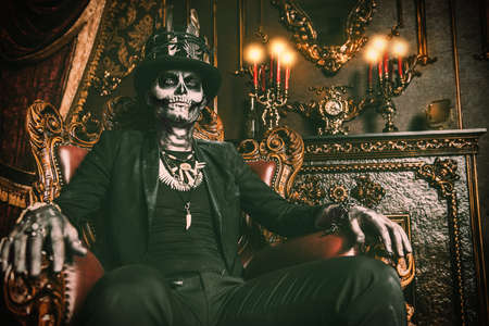 Halloween. A man with a skull makeup dressed in a tail-coat and a top-hat is in the old castle. Baron Saturday. Baron Samedi. Dia de los muertos. Day of The Dead. Old vintage interior.