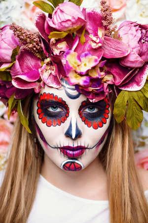 Dia de los muertos. Day of The Dead. Woman with sugar skull makeup on a floral background. Calavera Catrina. Halloween. Stock Photo