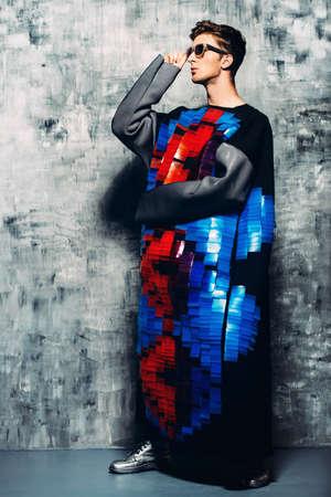 남자의 아름다움, 패션. 세련 된 옷을 입고 잘 생긴 남자 모델의 전체 길이 초상화. 스튜디오 촬영.
