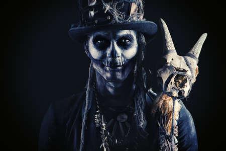 Un hombre con un maquillaje de cráneo vestido con un chubasquero y un sombrero de copa. Baron el sábado. Barón samedi Dia de los muertos Dia de los Muertos. Víspera de Todos los Santos.