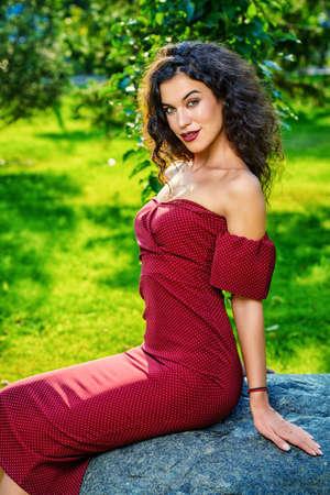 여름 공원에서 우아한 부르고뉴 드레스를 입은 매력적인 여자. 아름다움, 패션 개념입니다. 스톡 콘텐츠