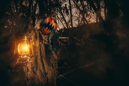 Personnage d'Halloween. Une terrible lanterne avec une citrouille sur la tête se promène dans la forêt de nuit.
