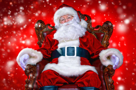 Christmas and New Year concept. Portrait of good old Santa Claus sitting in his armchair. Red background. 스톡 콘텐츠