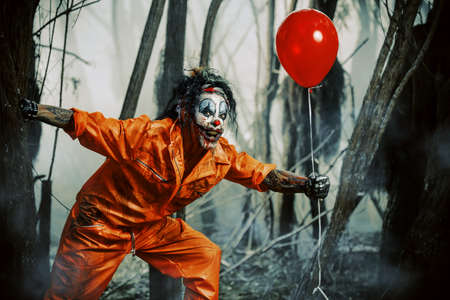 夜の森で、風船を使って血に染まる恐しい男ピエロ。男性ゾンビピエロ。ハロウィーン。ホラー。 写真素材