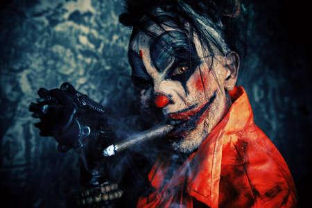 Verrückter schlechter Clownmann, der im Blut befleckt wird, raucht eine Zigarre und hält eine Gewehr. Halloween. Horror, Thrillerfilm.