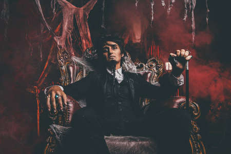 Halloween. Mysterious gloomy man in a black tailcoat in an old abandoned castle. The Dark Lord. Vampire man. Фото со стока