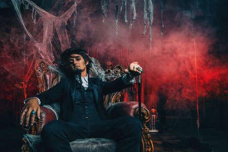 Halloween. Mystérieux homme sombre dans un manteau noir dans un vieux château abandonné. Le Seigneur des Ténèbres. Homme vampire. Banque d'images - 87261930