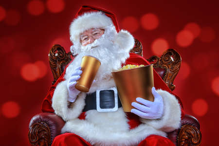 Merry Christmas and Happy New Year. Santa Claus sitting on his armchair and eating popcorn and drinking soda. Entertainment and cinema concept. Red background. Stock Photo - 87338551