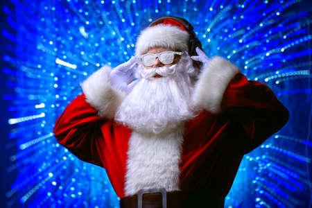 DJ Santa Claus en gafas de nieve y auriculares. canciones de Navidad y música. luces de discoteca en el fondo.