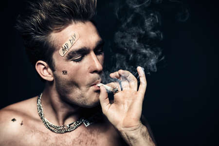 Antisocial behavior, bad habits. Portrait of a bad boy smoking cigarette. Rocker, punk. 版權商用圖片