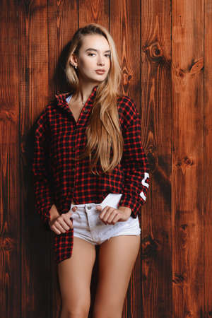 Portrait of a pretty blonde girl over wooden background. Beauty, youth fashion. Imagens