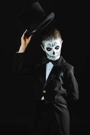 카니발 메이크업 우아한 꼬리 코트를 입고 해골의 자식 소년의 초상화. 스튜디오 검정 배경 위에 쐈어. 할로윈. Dia de los muertos. 죽은 자의 날.
