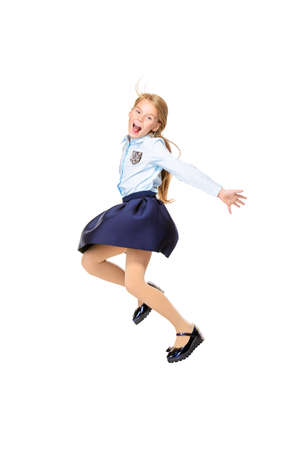 Happy excited schoolgirl in school uniform jumping for joy. Isolated over white background. School fashion. Copy space. Stock Photo