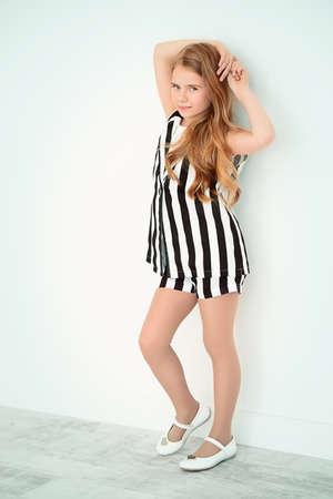 Menina bonito em um terno bonito do verão que levanta pela parede branca. Moda infantil. Foto de archivo - 87665540