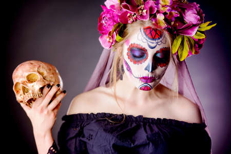 Calavera Catrina in black dress holding a skull over dark scary background. Sugar skull makeup. Dia de los muertos. Day of The Dead. Halloween. Stock Photo