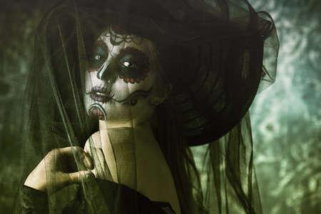 Portret van een mooie en enge Calavera Catrina in zwarte kleding en zwarte hoed met een sluier over donkere achtergrond. Suiker schedel make-up. Dia de los muertos. Dag van de Doden. Halloween. Stockfoto - 87665591