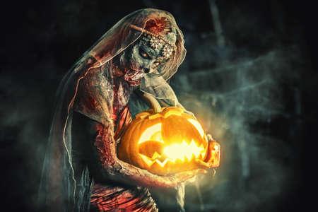 Halloween. La sposa spaventosa di zombie su un cimitero di notte tiene una lanterna di zucca. Archivio Fotografico - 87870243