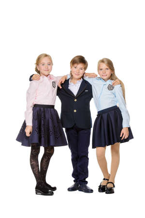 School fashion. Three happy children in school uniform posing at studio. Isolated over white background. Copy space. Full length portrait.