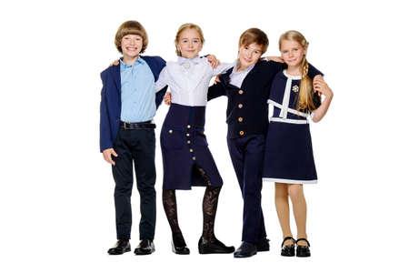 School mode. Groep gelukkige kinderen in schooluniform poseren in de studio. Geïsoleerd op witte achtergrond. Kopieer de ruimte.