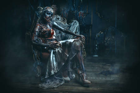 Zombie bride. Bloody dead bride woman in the old abandoned castle. Halloween. Horror. Stock Photo