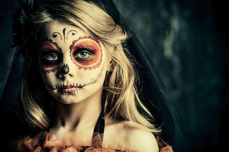 Portrait of a child girl in a costume of Calavera Catrina over dark grunge background. Little girl with sugar skull makeup. Halloween party. Dia de los muertos. Day of The Dead. Stock Photo